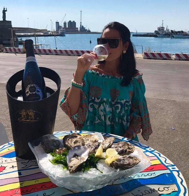 ragazza beve vino e mangia ostriche