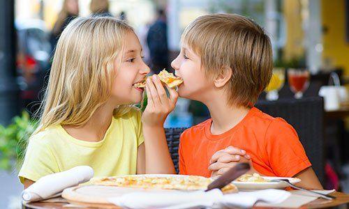 Bambini felici che mangiano pizza sorridente