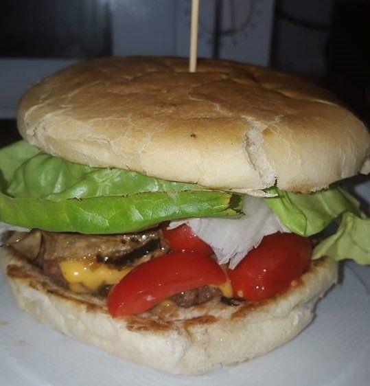 un panino con carne,insalata e pomodori