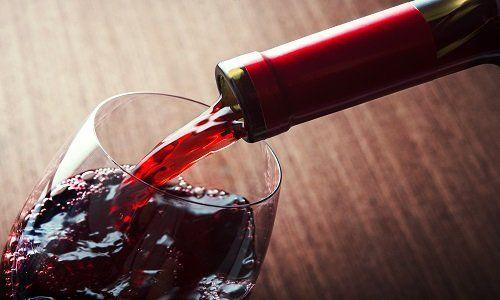 una bottiglia che versa del vino rosso in un bicchiere