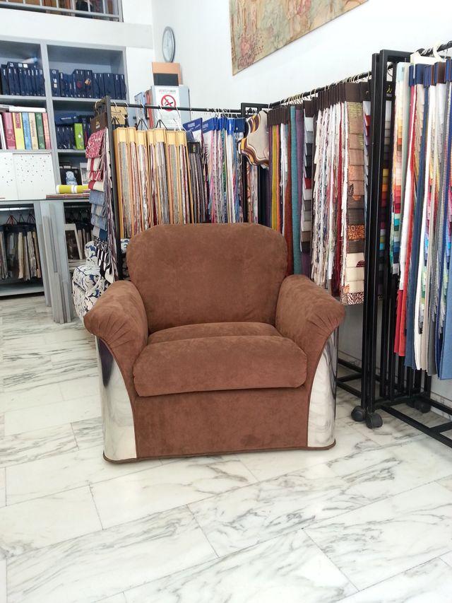 poltrona in stoffa marrone circondata da cataloghi stoffe colorate in esposizione