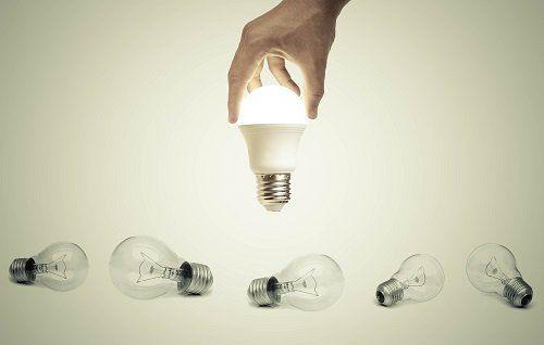 Mano tenendo una lampada accesa tra varie lampadine squallide