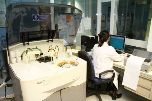 interno del laboratorio con un macchinario con l'oblo' aperto e  una donna con un camice bianco seduta alla scrivania mentre scrive al computer