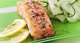 piatto di salmone  al forno con contorno di verdure e due spicchi di limone