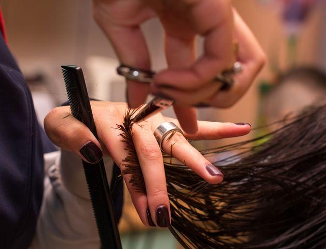 una parrucchiera che taglia i capelli di una donna con una forbice