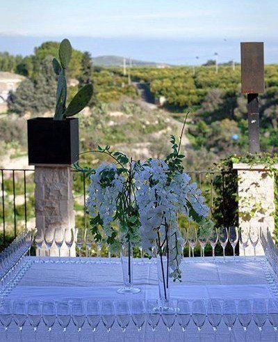 Perimetro di tavola coperto di coppe, fiori bianchi