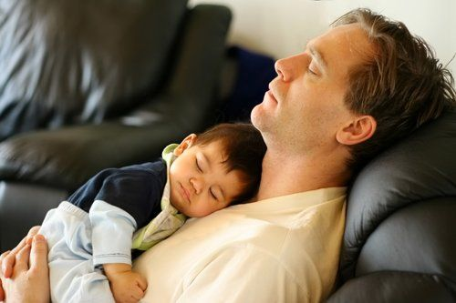 Young baby sleeping on his father chest