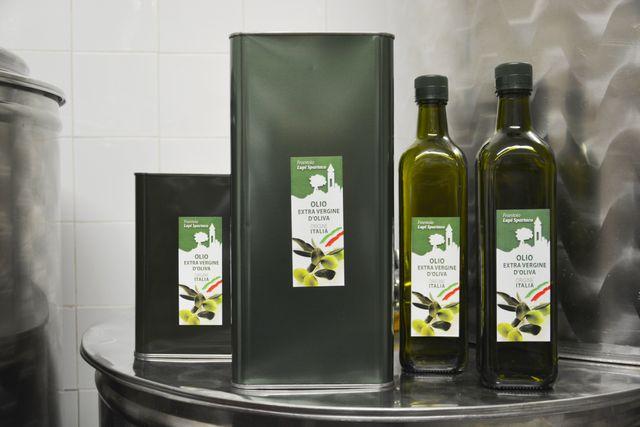 una bottiglia di olio extra vergine di oliva e accanto una tanica grigia