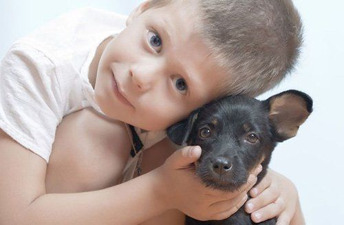 Young kid with a cute black puppy in Rice Lake