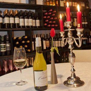 tavolo con calice di vino bottiglia e candelabro davanti a un assortimento di bottiglie