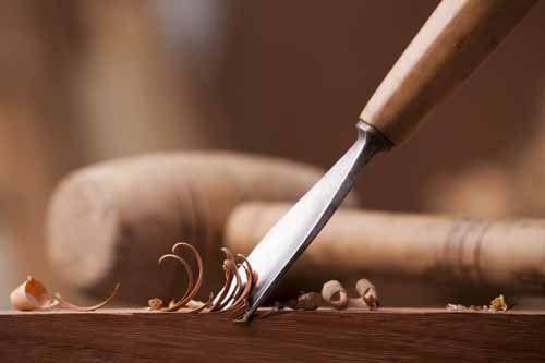 primo piano di un carpentiere mani con uno scalpello e martello sul banco