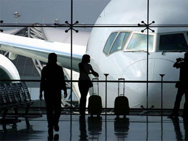 vista attraverso i vetri di un aeroporto di un aereo gia' atterrato e l'ombra di alcune persone con delle valigie a rotelle a Salsomaggiore Terme, PR