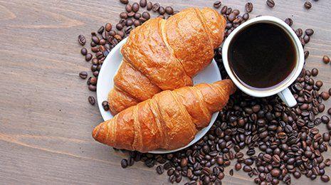 Caffè, cornetti e chicchi di caffè vista superiore su sfondo tavolo in legno
