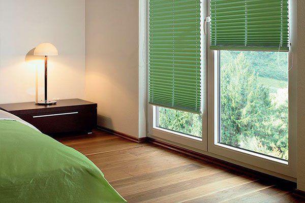 Porta-finestra basculante di PVC bianco con persiane laminate verdi