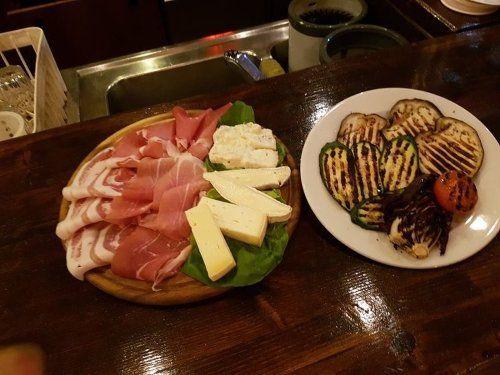 Piatto di verdure grigliate e piatto di formaggio e prosciutto
