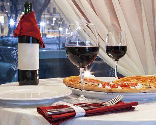 Pizza, bottiglia e due bicchieri di vino