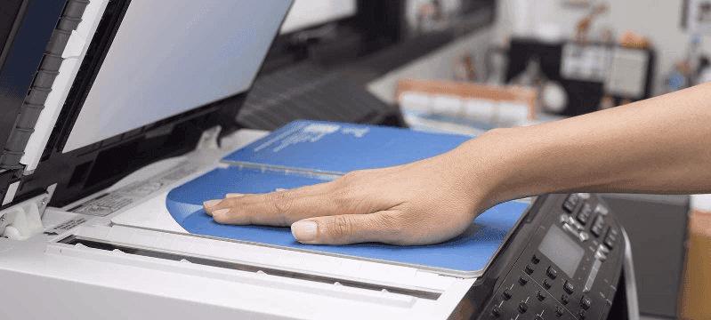 Una mano che preme un libro du una stampante