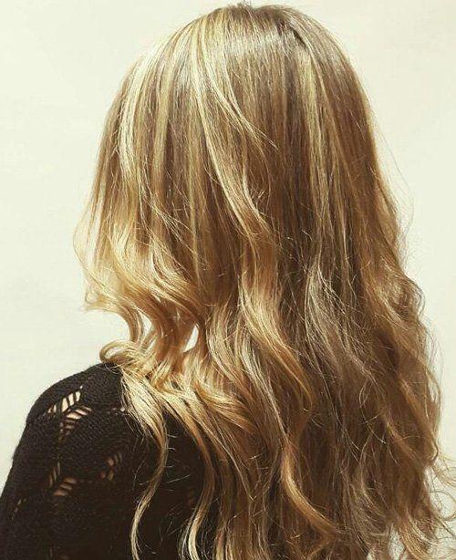 una ragazza con capelli biondi leggermente mossi vista dal dietro