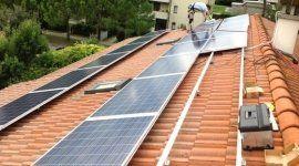 addetto mentre monta dei pannelli solari sul tetto