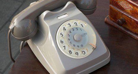 Vecchio telefono grigio con disco di marcatura