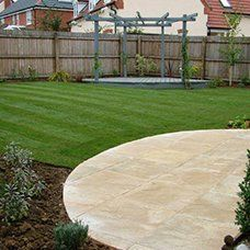 A new paved area with a circular edge and a freshly mowed lawn