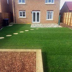 The back garden of a property with perfectly cut grass and stepping stones