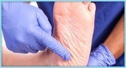 podologo con guanti mostra un piede