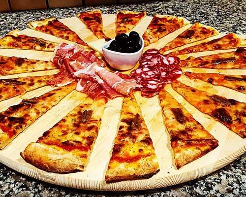 pizza tagliata a spicchi con salumi ed olive al centro