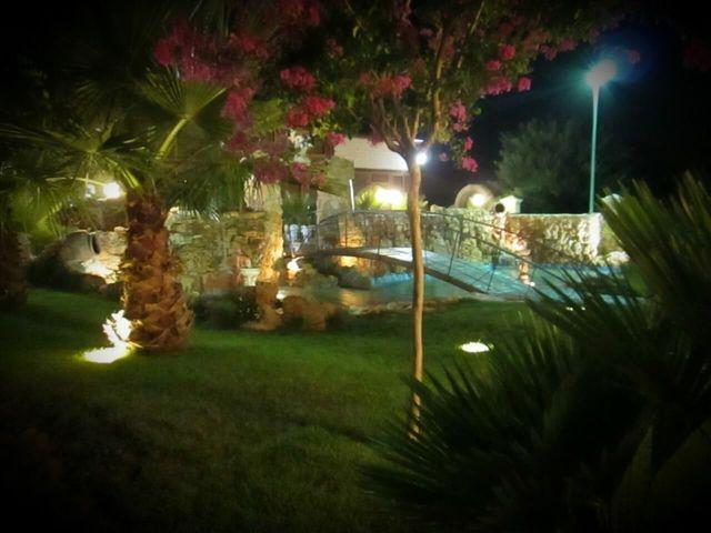 Delle  tavolate apparecchiate all'esterno in un giardino e vista di un ponte e dell'acqua che passa sotto