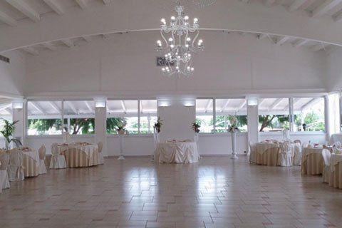 Una sala con dei tavoli con delle tovaglie bianche