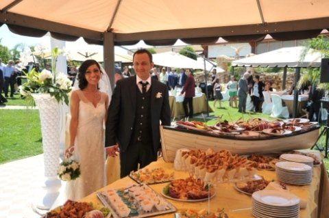 Una coppia di sposi davanti a un buffet e delle persone