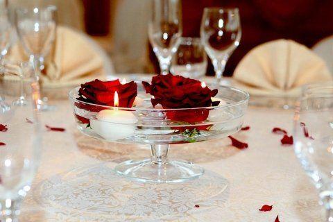 Una tavola con dei bicchieri e un vaso di cristallo con un lumino acceso e dei fiori rossi