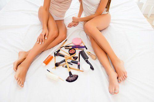 delle gambe di due ragazze e accanto dei trucchi