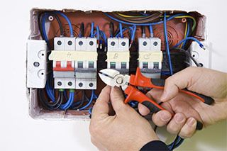 An electrician working on an electric panel upgrade