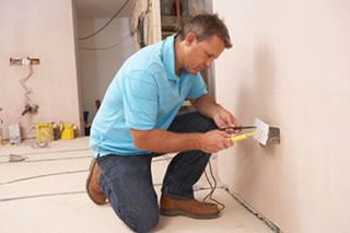 Residential Electrical Repairman working on an outlet