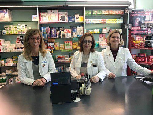 farmaciste sorridenti davanti alla cassa della farmacia