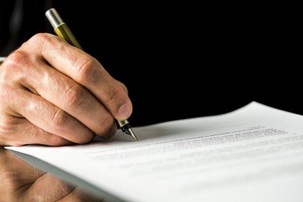 Mano di un'uomo firmando i documenti a Monteriggioni