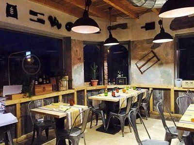 Donna burgherita a Merate - vista interna del ristorante con tavoli apparecchiati e lampade nere a sospensione