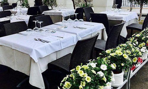 dei tavoli apparecchiati e dietro una fioriera all'esterno di un ristorante