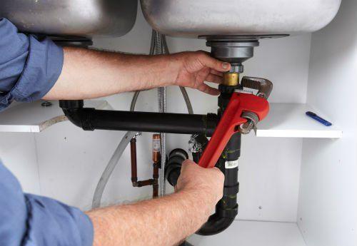 due mani di un idraulico mentre stringe un bullone sotto un lavandino