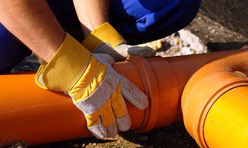 Primo piano delle mani idraulico montaggio tubazioni di scarico in pvc a casa fondazione