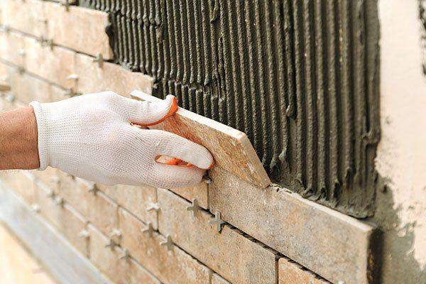 una mano con un guano che posiziona un mattone su del cemento fresco