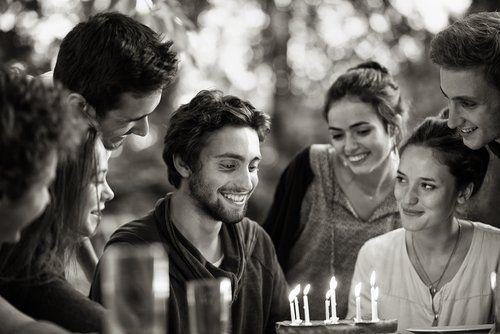 amici intorno al festeggiato che guarda la torta con candeline