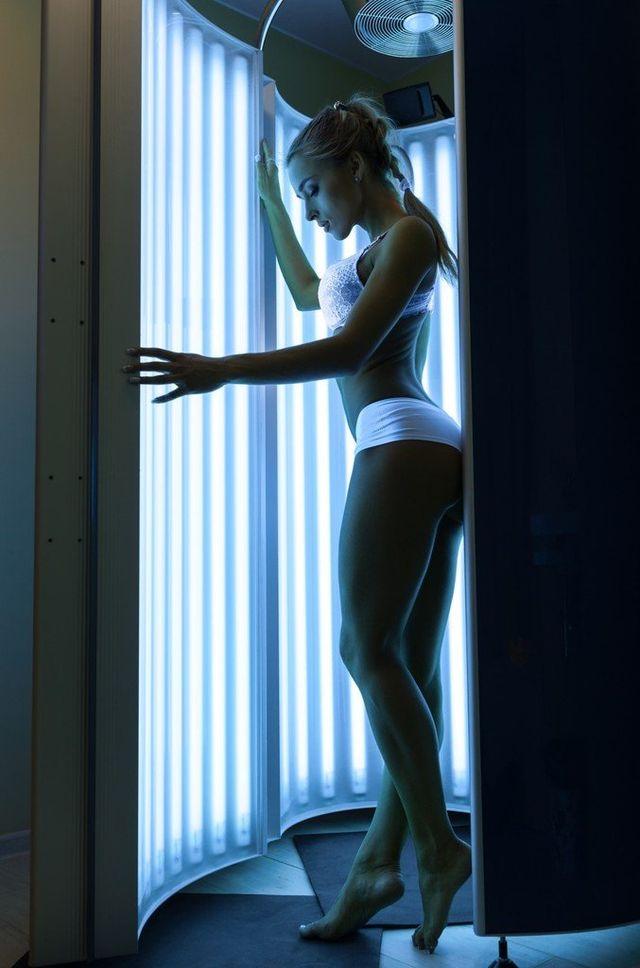 lettino da massaggio in una stanza con luci soffuse e candele accese