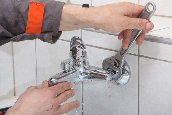 un idraulico che stringe il tubo di un rubinetto con un pappagallo cromato