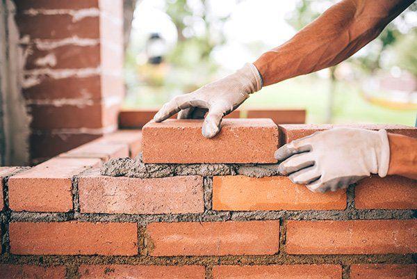 due mani con dei guanti che posizionano dei mattoni su del cemento fresco