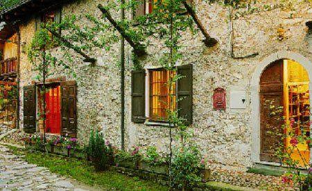 vista di una facciata in pietra e delle finestre in legno