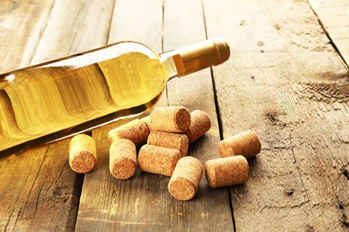 una bottiglia di vino bianco e dei tappi di sughero