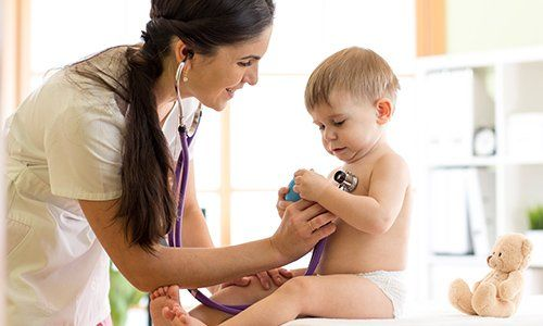 Dottoressa asoltando il cuore di un bambino