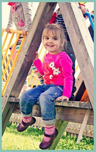 Little girl sat on a wooden playground